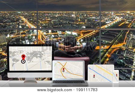 Back side of sitting businessman who is looking at express way with cityscape out off windows glass with Computer set show navigator map on traffic jam on the table Business transportation concept, 3D illustration