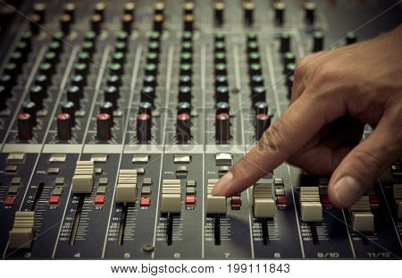 Closeup Hand adjusting audio mixer music instrument concept