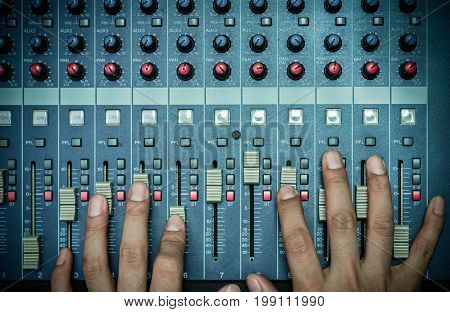 Top view of Hands adjusting audio mixer music instrument concept