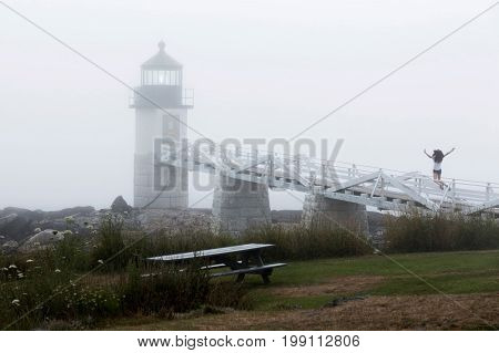 Thick fog is covering the Marshall Point Lighthouse on an early August morning. There is also a teenage girl jumping in the air on the wooden walkway