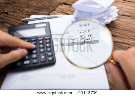 Cropped image of businessman examining invoice with magnifying glass by calculator at table