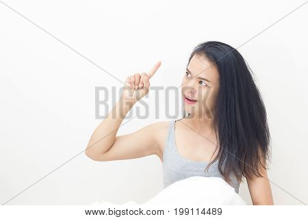 young woman wakes up in her bed with a white blanket. Along with stretching in bed after waking up. The concept of lifestyle and good health.