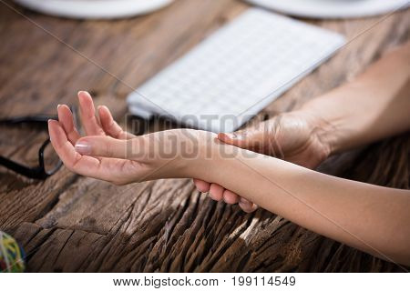 Close-up Of A Businessperson Holding Painful Wrist Over Wooden Desk