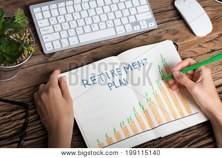 Elevated View Of A Human Hand Drawing Retirement Plan Growth Concept On Notebook