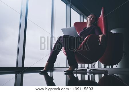 Tired and relaxed boss woman with laptop is sprawling in bent red armchair in office chill out area and dreamy looking up with copy space place for logo your text or other advertising