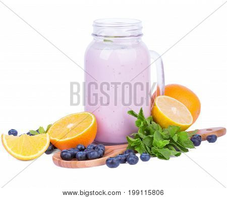 A beautiful composition of a mason jar with milkshake, juicy oranges, spoon with blueberries and mint leaves isolated on a white background. Refreshing summer drinks and desserts. Copy space.