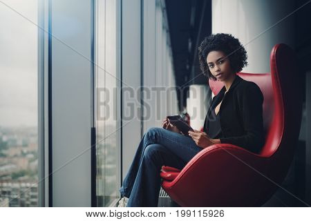 Young cute biracial female probationer holding digital tablet while sitting on red armchair in office interior hall with reflections next to window and column cityscape outside