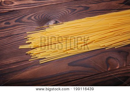 Long yellow noodles on a brown wooden table background. Traditional italian restaurant cuisine. Spaghetti pasta full of carbohydrate. Homemade italian dishes full of nutrients.
