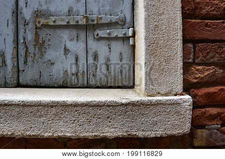 An old window with a wooden shutter in a derelict building in the Dorsoduro quarter of Venice