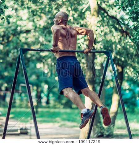 Senior Man Exercising Outdors In Public Park, Toned Image, One Man Only