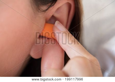 Close-up Of A Woman Putting Earplug Into Her Ear