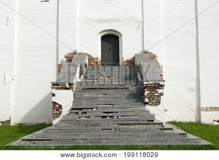 grey stone staircase leads up to a metal door in the wall of the white building porch grass stage
