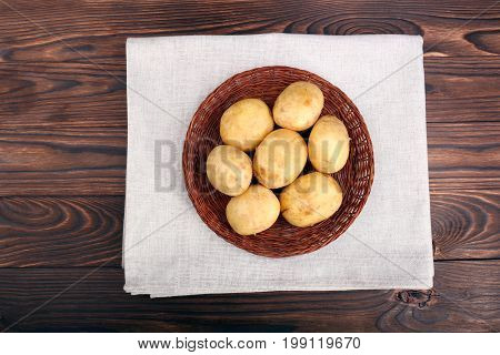 New and raw potatoes in a wattled plate, young unpeeled potatoes for delicious courses, vegetables containing substances necessary for growth, health, and good condition on a dark brown background, top view.