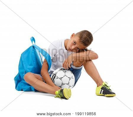 A tired boy sitting on the ground. A little soccer player isolated on a white background. Outdoors activities. Sports concept. A sportive kid with a soccer ball. A teenager in sports form. Copy space.