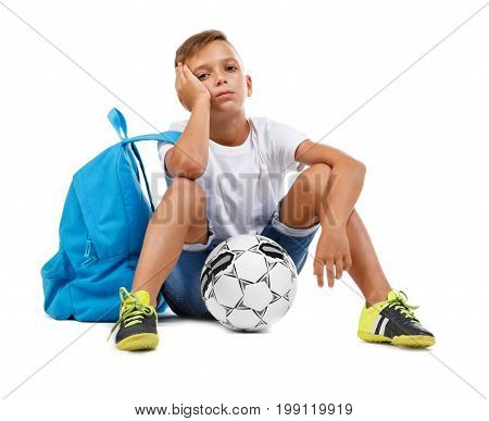 A sad tired boy sitting on the ground and thinking. A sportive kid with soccer ball. A little soccer player isolated on a white background. Outdoors activities. Sport concept.