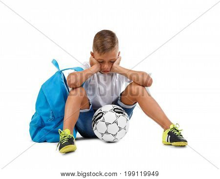 An upset footballer boy sitting on the ground. A little soccer player isolated on a white background. Outdoors activities. A sportive kid with soccer ball. School and sports concept. Competition concept.