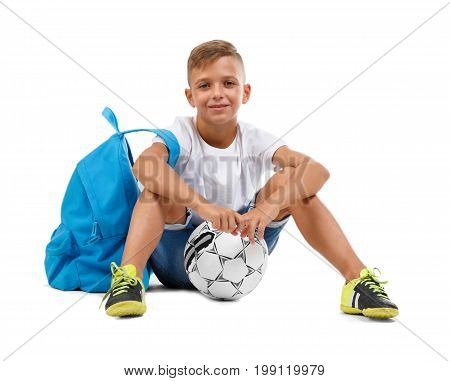 Happy little boy isolated on a white background. A smiling kid with a ball and a blue satchel sitting on the ground in a yoga pose. Lucky schooler with a soccer ball. School and football concept.