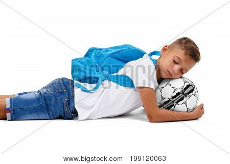 A little boy with a head on a ball. A cute tired soccer player lying on the ground and sleeping. A sportive schooler with bright blue rucksack isolated on a white background. Childhood concept.