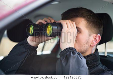 Close-up Of A Man Sitting Inside Car Looking Through Binocular