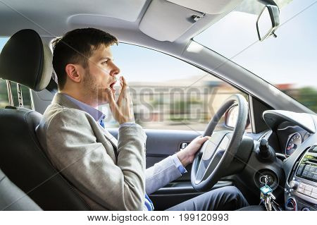 Side View Of A Young Man Yawning While Driving Car