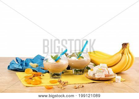 A composition of two dessert glasses filled with thick beverages isolated on a white background. Banana smoothie with decorative mint leaves, physalis and bright blue straws on a light wooden table.