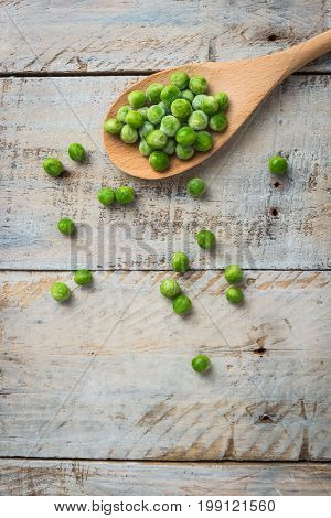 Fresh frozen peas on a spoon. Vegetable food background healthy vegetarian natural meal.