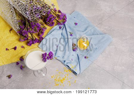 A view from above on a margarita glass full of milk cocktail and colorful fabric on a gray table background. A glass of milkshake with decorative flowers. Refreshing smoothie with a purple bouquet.