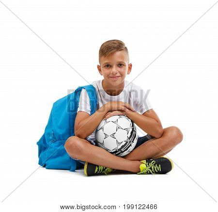 Happy little boy isolated on a white background. A smiling kid with a ball and a blue satchel sitting on the ground in a lotos pose. Lucky schooler with a soccer ball. School concept.
