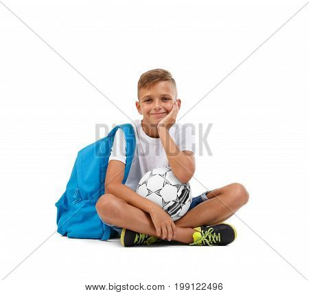 Smiling little boy isolated on a white background. A happy kid with a soccer ball and a blue satchel sitting on the ground in a joga pose. Lucky schooler with a shining face. Sports concept.