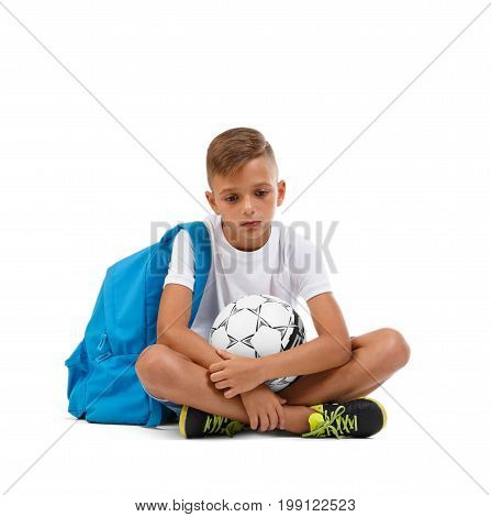 An upset boy sitting on the ground in a yoga pose. A little soccer player isolated on a white background. Outdoors activities. Sport concept. A sportive kid with soccer ball. Copy space.