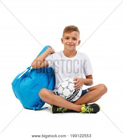 Cute little boy isolated on a white background. A smiling kid with a ball and a blue satchel sitting on the ground in a yoga pose. Joyful child with a soccer ball. School concept.