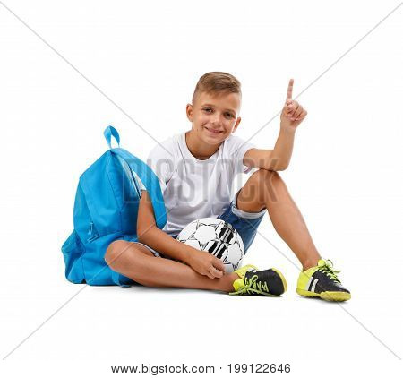 Little kid isolated on a white background. A smiling boy with a ball and a blue satchel sitting on the ground. Lucky schooler with a soccer ball. Competition game concept. Championship concept.