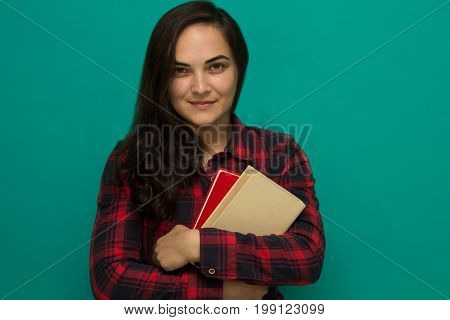 young girl student in a red plaid shirt with books