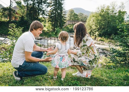 happy family play with daughter near the river in mountains, old bridge on backgeound