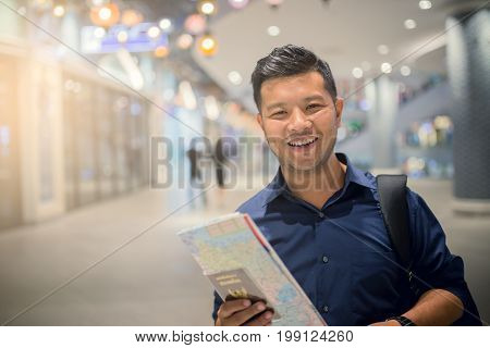 Asian men are using smartphone smiling happy inside office building airport waiting for plane for traveller in the airport terminal. Traveling concept.