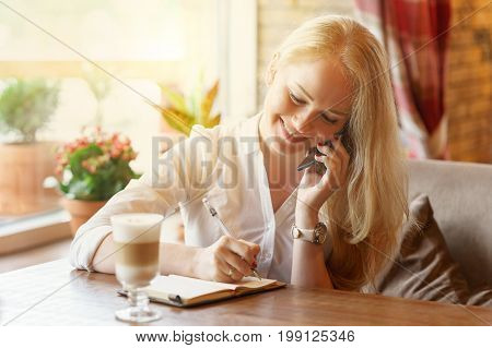 young blonde caucasian woman with happy smile is writing some message note or letter in her notebook talking by phone at day time
