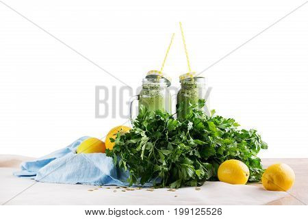 Two mason jars full of healthful green smoothies on a blue fabric, isolated on a white background. Smoothies from celery, parsley, spinach, and cucumber. Lemons, zucchinis, branches parsley on a desk.