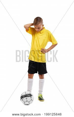 Full-length photo of an adorable teenager wearing a yellow football uniform, isolated on a white background. A non-confident boy looks at the ball and holds his head. Sport and healthful concept.