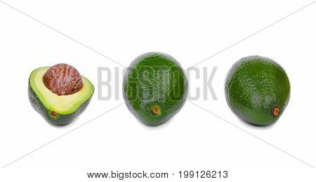Two whole green avocados and one cut in half, isolated on a white background. An organic, fresh, and ripe avocado with a large stone. Three healthful and colorful fruits in a row.