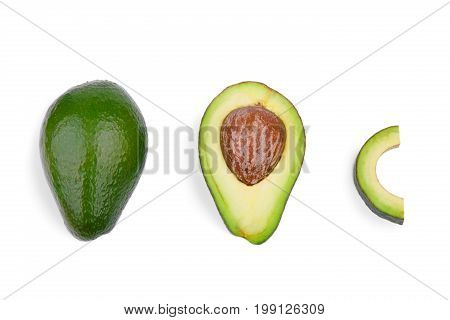 A top view of a whole, a cut in half and a slice avocados, isolated on a white background. A fresh and natural avocado with a large stone in a center of composition. Three healthful fruits in a row.