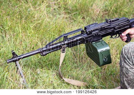 Machine gun Pecheneg. A soldier is holding a machine gun by the handles.