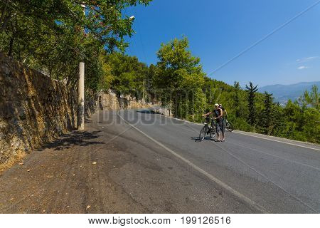 ALANYA TURKEY - JULY 09 2015: The hard way up the hill. Cyclists go on foot. Alanya - a popular holiday destination for European tourists.