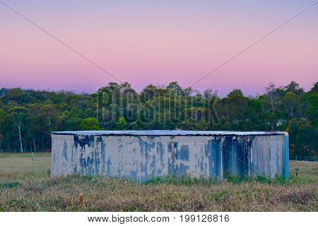 old bush property water tank in Perth hills Australia with a corrugated metal cover