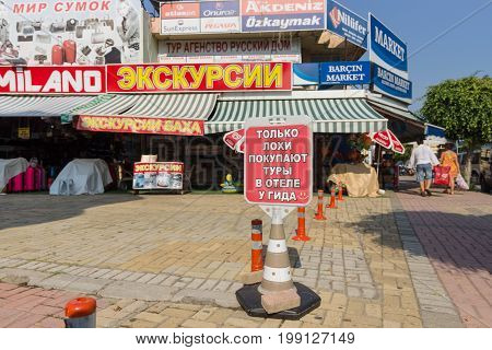 KONAKLI TURKEY - JULY 10 2015: Outdoor advertising sightseeing tours. In the foreground of advertising in Russian: Only losers are buying tour guides at the hotel.