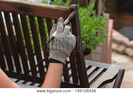 Painting and applying protective eco-friendly paint on a wooden garden chair.