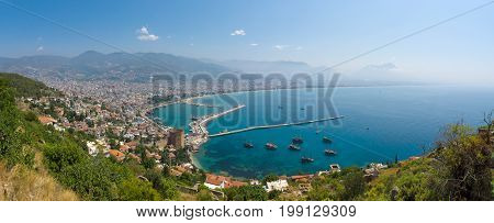 Panoramic view of sea port of Alanya. In the foreground the ruins of an ancient fortress. In the background of the Taurus mountains and residential neighborhoods of Alanya. Turkey.