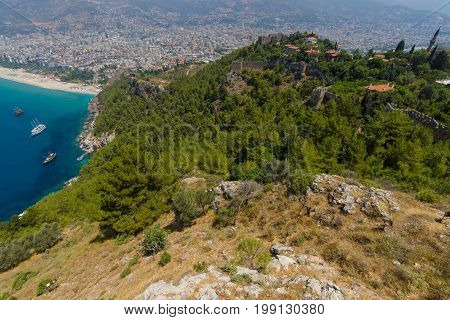 The fortress walls the ruins of the fortress of Alanya in the background the rooftops of the center of Alanya and the city beach. Turkey.