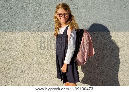 Outdoor portrait of an elementary school student in uniform with schoolbag.