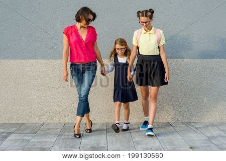 Mother and daughter students holding hands go to school. Back to school!