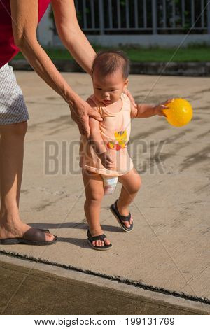 The boy is practicing walking with his grandmother closely supervised.  In the hands of a boy playing the ball.